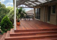 Pitched roof verandah over a stepped merbau deck. Clear laserlight roofing allows light to filter through