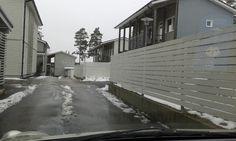 Yksinkertainen valkoinen piha-aita yhdistettynä kapearimaisiin suoja-aitoihin sisäänkäyntien/varastojen yhteydessä. Kauklahti.