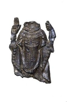 Part of a pilgrim badge, possibly from the shrine of St Thomas Becket at Canterbury Cathedral. This badge depicts a bishop or a saint wearing vestments. His right hand is raised in a gesture of blessing. His left hand is holding a staff. The figure's head and lower body are missing. The figure may be that of St Thomas Becket. 13th-15th century | Museum of London