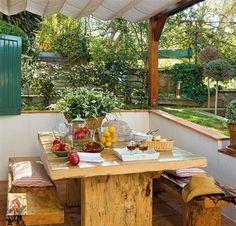 Comedor exterior con mesa y bancos de madera bajo pérgola