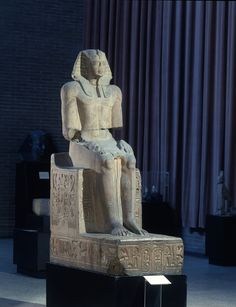 Heroic seated statue of Ramesses II. Enthroned king has traces of red on flesh and wears blue / yellow striped Nemes headddress.