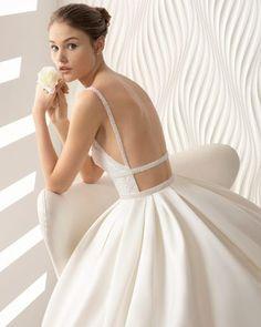 Noivas que desejam usar modelos com tecidos exclusivos e inovadores. Este belíssimo modelo tem um decote em V de brilhantes e renda. As costas totalmente abertas com alças com brilhantes conferem glamour e sensualidade. O tecido de otomano da saia junto a