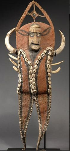 Papua New Guinea | A karahut ~ Abelam/Maprik ~ pectoral | Woven fiber panel applied with a carved head, cowrie and nassa shells, and boar's tusks, over-modeled with clay and painted in red and black. | Est. 2,000 - 3,000$