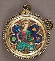 "Locket, 14th century, French, basse taille enamel, silver gilt. This pendant once contained a small disk of wax, blessed by the pope during the Easter season and worn as a kind of amulet. The back shows a lamb, a symbol of Jesus, and is surrounded by a Latin inscription that translates: ""Lamb of God, who takes away the sins of the world, have mercy upon us."" Pregnant women sometimes wore such pendants for protection."