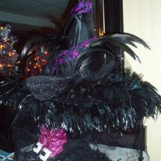 Hocus Pocus ... Witch hat with veil added string of feathers to brim set on wood pedestal draped black boa with witch shoes underneath on my buffet table for Halloween.