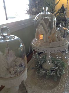 cloche and putz glitter houses on pretty cake plates for a white christmas