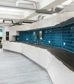 Workplace kitchen >> This curved kitchen at the workplace of the Manchester Growth Company provides an interesting formation to compliment the sleek white gloss kitchen units and teal blue gloss tile splashback in a brick arrangement. Primary colours are used throughout this Manchester office design to maintain a modern, innovative feel. See more of this project on our website...