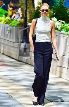 Karlie Kloss wears a cropped turtleneck tank with wide-leg trousers and black ballet flats