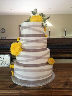 Gray and yellow wedding cake. Yellow flowers. Gray ribbon
