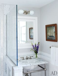 In a bath, the light fixture, washstand and fittings, and marble tiles are all by Waterworks | archdigest.com