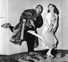 "LET'S DANCE: Charles Laughton and Rita Hayworth casually kick up their heels on the set of ""Salome."""