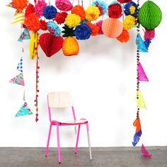 Qué decorado tan divertido hecho con farolillos, banderines y pompones de colores!