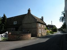 Angle End Cottage House formerly the Grapes P.H., dated 1741, enlarged late c1970's at rear. Gault brick with red brick dressings to doors, windows and quoins with  steeply pitched plain tiled roof. Saw tooth eaves, cornice and end parapets on red brick  kneelers