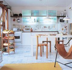 Sem barreiras visuais, cozinha e sala formam um só conjunto. Móveis brancos e piso claro em mármore são fundamentais para unificar os espaços, onde a frieza é quebrada pelos móveis em madeira e couro.