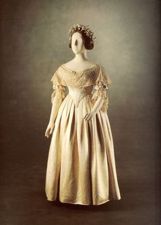 Queen Victoria decided against the traditional royal silver wedding dress and wore a dress of rich pure white satin, trimmed with orange flower blossoms. The lace which formed the flounce of the dress was Honiton lace; it measured four yards, and was three quarters of a yard wide.