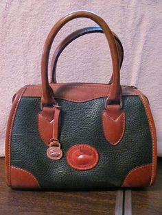 This stylish bag from Dooney-Bourke is the perfect blend of fashion and function  Hits all the style notes  This bag is a must have  DOONEY BOURKE  WOMENS ALL WEATHER LEATHER  SATCHEL HANDBAG  EXCELLENT CONDITION  FOR PREOWNED  SMALL MARK ON RIGHT SIDE  BACK OF PURSE  SEE PICS  GREEN/BROWN LEATHER  METAL FOB  8 IN HEIGHT  10 1/4 IN LENGTH  7.5 IN DEEP  5 IN STRAP DROP  AWESOME HANDBAG  WONDERFUL ADDITION  TO YOUR WARDROBE