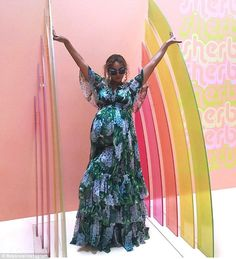 Bright: The Dreamgirls star was then pictured standing with her arms flung upward to touch two multicolored rainbow-shaped screens protruding from the pink wall behind her