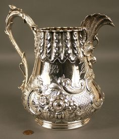 Coin silver pitcher with lily handle and elaborate floral and cartouche chasing, marked J.E. Caldwell & Co.Philadelphia, purchased by Major Joseph Cloyd, November 4, 1851