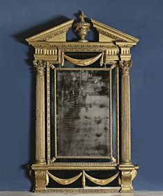 AN IRISH GEORGE II GILTWOOD MIRROR  BY JOHN & FRANCIS BOOKER, CIRCA 1750  With later central plate & border plates, the frame with Corrinthian column uprights & Greek pediment cresting centred by an acanthus vase, the base with lappeted scrolled supports, the reverse with the shadow of the trade label of Francis & John Booker of Essex Bridge, Dublin, later applied onto a separate Phillips & Harris' card, the plates and applied drapery largely replaced, regilded in the 19th Century   68 x…