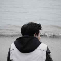 Rear View Of Man Wearing Hooded Shirt Sitting At Sea Shore
