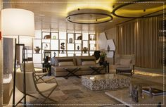 Sala de estar com escritório por Debora Aguiar, teto de madeira , sofá bege e almofadas em tons neutros, abajur de madeira e poltronas contemporâneas. Painel com nicho de madeira e iluminação de fundo