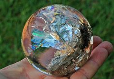 Stunning Rainbow Quartz Rutile Sphere    Clean quartz with feldspar as rutile needles bed and sparkling rainbow foils.