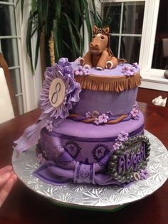 Purple Horse cake. Top tier: Chocolate cake with vanilla mousse filling covered in buttercream icing. Bottom tier: Grape and yellow checkerboard cake covered in hand painted bandana fondant. Gum paste #8 purple ribbon. Fondant horse, belt buckle, fringe, horseshoes, and flowers.