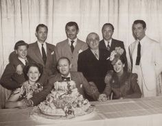 MGM stars (top) Mickey Rooney, Robert Montgomery, Clark Gable, Louis B. Mayer, William Powell, Robert Taylor, (bottom) Norma Shearer, Lionel Barrymore and Rosalind Russell at Barrymore's birthday celebration in 1939