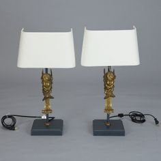 Pair of 19th Century Bronze Puti Cherub Lamps --- 19th century bronze puti form the base of this pair of table lamps. Assembled with modern elements and shades, these antique elements make striking fixtures for a bedroom, library or living room. Height measurements are without shades to top of sockets. --- Item:  3312 --- Retail Price:  $2995