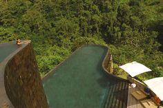 Ubud Hanging Gardens, Bali  Inmitten der steilen Reisterrassen Balis liegt der große Panorama-Pool des Ubud Hanging Gardens. Er ist terrassenförmig angelegt und erstreckt sich über zwei Ebenen. Mit seiner natürlich geschwungenen Silhouette und seinem klaren Wasser in gedämpften Blau-Grün-Tönen passt er perfekt in die tropische Umgebung.