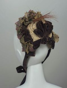Beige and brown straw bonnet with brown velvet ribbons, artificial ivy leaves, clusters of blueberries and a spray of brown feathers, American (California), 1877-80.