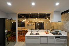 作業中に天板がごちゃごちゃしがちなキッチンは、手元が隠れる程度の高さの壁でリビング側から目隠し。