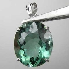 An amazing green amethyst pendant 34.10 CT. This twinkling gemstone is a huge 21. X 18. MM oval cut set in white gold plate.