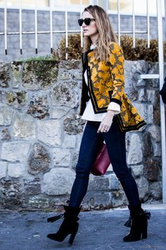 Dark blue denim tucked into black boots with a statement coat.