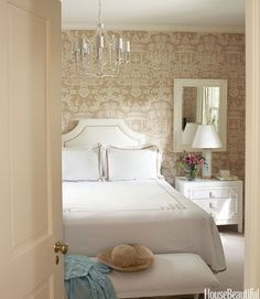 """In a Palm beach guest bedroom, Lhasa Camel wallpaper from Brunschwig & Fils picks up the theme. Designer Meg Braff bought the vintage chest and then found linens by Jane Wilner with a similar fretwork motif. She added Oly's Claire bench """"so the first thing you see from the living room isn't the bed."""" The light fixture is vintage: """"I'm a great fan of vintage fixtures. They bring a lot of personality.""""   - http://HouseBeautiful.com"""