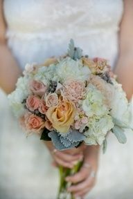 """The bridesmaids' bouquets will be a clutch of cream hydrangeas, peach """"juliet"""" garden roses garden roses, pale pink ranunculus, ivory spray roses, white mini calla lilies, and grey dusty miller wrapped in grey ribbon."""