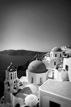 Black and White Photo of buildings on a cliff with blue domed rooftops in Santorini, Greece, with a view of the Aegean sea in the background © John Bragg Photography
