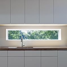 window in the splashback. This one is small enough to show just enough and the greenery would cover the fence, could still get the subway tile splash back around it if you wanted or a nice muted grey glass or perspex solid splashback? Cupboards are nice too mumma
