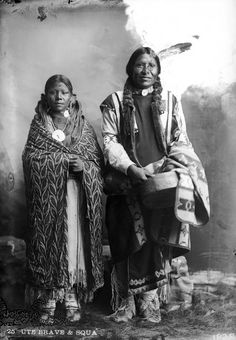 Standing studio portrait of unidentified Native American (Ute) man and wife. - 1880/1900