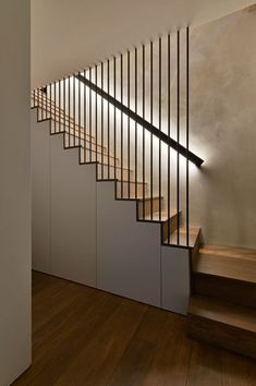 These modern wood stairs have a handrail with hidden lighting, and a floor-to-ceiling steel rod safety barrier. Square Feet Architects have designed modern stairs that have handrails with hidden lighting, and floor-to-ceiling steel rods safety barriers.