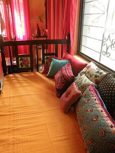 A divan with a great set of pillows pulling together many different colors and patterns beautifully.