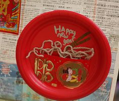 CNY decoration - noodles!  Using paper plate, lucky red envelope, yarn.