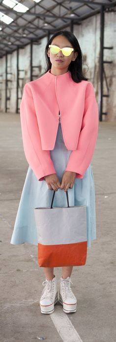 Australia fashion week street style: a pale blue dress and neoprene pink jacket with platform sneakers and mirrored sunglasses