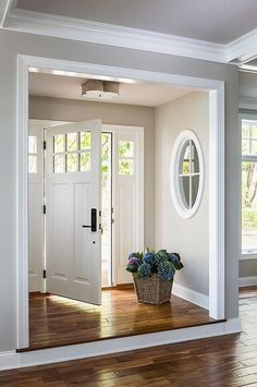 Step up leading to foyer nook, gray walls with interior window and white molding Casa Verde Design Style At Home, Interior Windows, White Interior Doors, Front Door Design, House Door Design, Entry Doors, Front Entry, Entrance Foyer, House Entrance