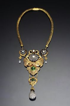 A mid-Victorian style diamond & emerald-set gold Necklace   India, 19th Century. Large repousse pendant with chased detailing pendant in the form of a scrolled cartouche, set with a large oval diamond-set plaque, a large emerald & further diamonds, above a suspension fitting in the form of a diamond-set rosette each with a diamond suspension, below a further pendant with foliate flourishes set with an emerald & a large pave diamond-set drop, on a fancy-link gold chain with chased decoration