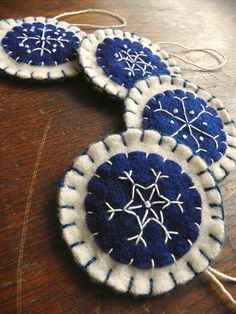 Scissaroo - This is a hand embroidered snowflake ornament. I embroidered the snowflake using white thread onto a lovely dark blue circle. More