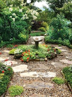 Large flagstone pavers, surrounded by pea gravel, create a rustic, winding path in this lush backyard that's filled with blooming perennials and ornamental trees.