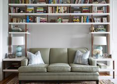 Contemporary Vintage Bookshelf: Tall white shelving above green couch..
