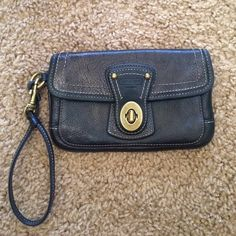 Coach black leather wristlet Gold detail and buckle make this wristlet stand out!  Satin striped lining shows some wear but can be removed at dry cleaner. Two pockets will separate your phone from your credit cards/lip gloss.  Gently loved but still in great shape! Coach Bags Clutches & Wristlets