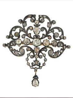 A 19th century diamond brooch. Of openwork scrolling foliate design, set with foiled rose cut diamonds, with a foiled pear-shaped rose-cut diamond drop, circa 1890.